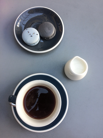 Coffee and macaroons on a blue plate on a light table background 版權商用圖片