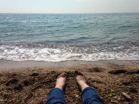 The girl in jeans lies on the persian on the sea in sunny weather 版權商用圖片