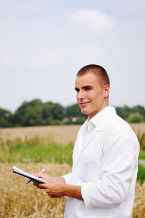 Young agriculture specialist taking notes about his experiment in the wheat field photo