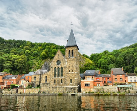 View of old church in Dinant from the river Meuse, Belgium in cloudy day with dramatic sky photo