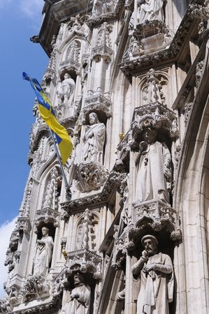 Angle view of gothic statues from medieval facade of city hall on Grand Place in Leuven, Belgium with local province flag Stock Photo - 16916846