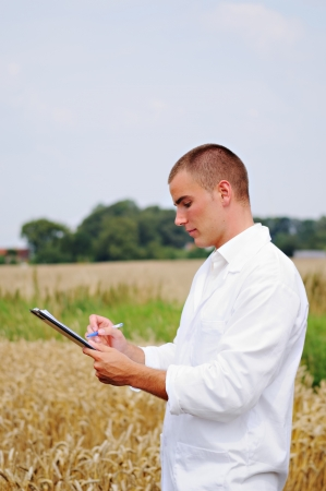 Young agriculture specialist taking notes in the wheat field