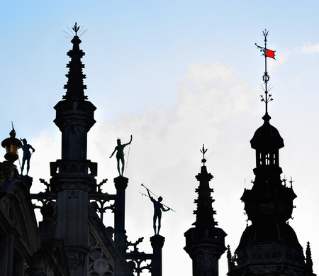 silhouettes in gothic style against sun of medieval building on Grand Place in Brussels, Belgium
