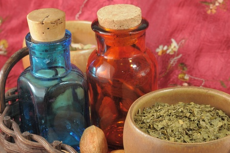 stimulator: Vintage medical bottles and a mix of dry herbs on red runner