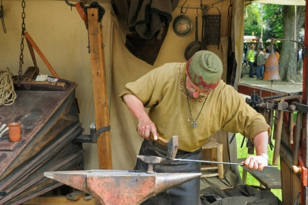 ancient blacksmith: BRUSSELS, BELGIUM-MAY 19  Unidentified performer shows art of a blacksmith during Medieval Market celebration in Cinquantenaire Parc on May 19, 2013 in Brussels, Belgium Editorial
