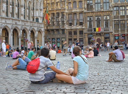 expected: BRUSSELS, BELGIUM - JULY, 21  Tourists follow tradition to sit on Grand Place stones during National Day of Belgium on July 21, 2013 in Brussels  This day Brussels expected 500000 guests Editorial