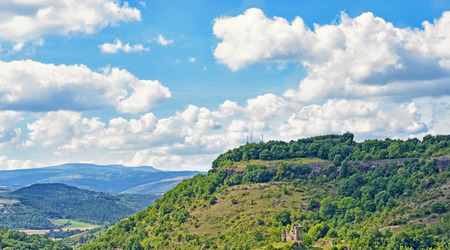Mountain landscape in Auvergne region of France with ruins of a small medieval castle on hillside photo