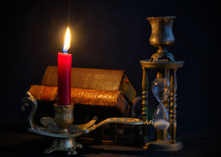 Vintage candlestick with red candle, books and  hourglass  in dark room