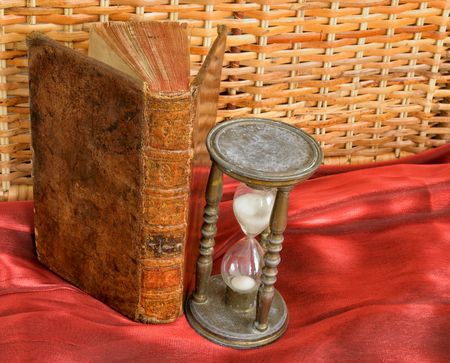 Vintage book and hourglass on old table closeup image photo