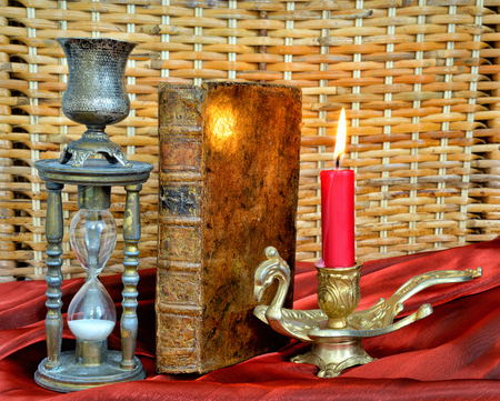 Magic book, firing candle and hourglass on vintage table photo