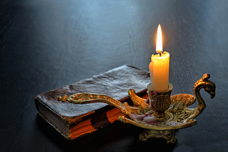 Antique book and firing candle on a dark table backlit in evening photo