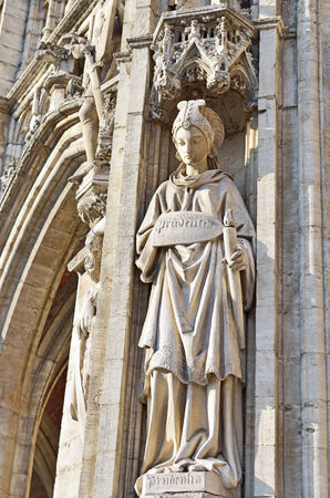 heads old building facade: statue of Prudence from medieval facade of City Hall on Grand Place in Brussels, Belgium