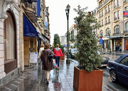 louise: BRUSSELS, BELGIUM-AUGUST 20, 2014: People walk during rain on avenue Louise. This is mostly expensive shopping street in Brussels