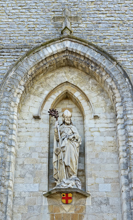 city coat of arms: Statue of the saint on entry to Saint Sevatius or Sint Servaas church in Wemmel, Belgium with attributes of the city Wemmel - coat of arms and cross