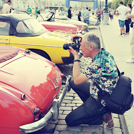 BRUSSELS, BELGIUM-SEPTEMBER 07, 2014: Tourist takes a picture of a vintage car exposed during Comic Book Festival on Place des Palais. Vintage look filtering applied