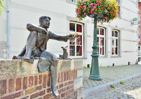 ber: MAASTRICHT, NETHERLANDS-JULY 07, 2014: Statue of a boy and a dog or Pieke oet de Strokstraot illustrating the novel of Lambertus Cornelis - Ber Hollewijn