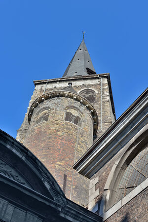 wallonie: Medieval walls are covered by special metal net to protect pedestrians on the street walking near Collegiate church of Saint-Denis of Liege. The church was founded in 10 century