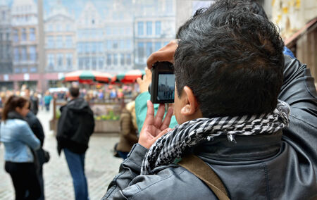tourists stop: BRUSSELS, BELGIUM-OCTOBER 23, 2014: Cold weather does not stop tourists from crowding historical center of Brussels. Foreign tourist takes pictures on Grand Place Editorial