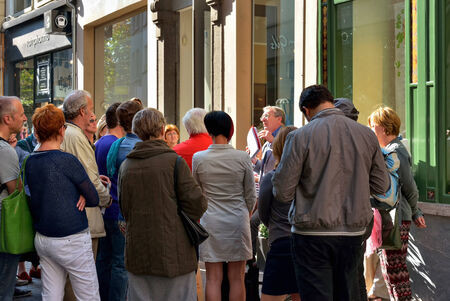 guided: ANTWERP, BELGIUM-OCTOBER 04, 2014: Tourists listen with attention their guide on the street of Antwerp. Because of events commemorating World War I the city accepted about 100000 visitors