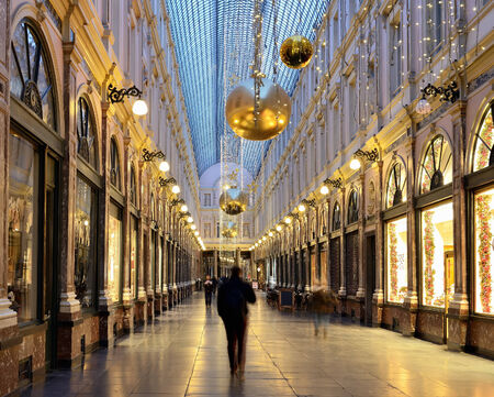BRUSSELS, BELGIUM-DECEMBER 8, 2014: People traversing decorated for Christmas Royal Galleries Saint Hubert in early morning visible as blurred silhouettes. The Galleries are one of main attractions of Brussels Editorial
