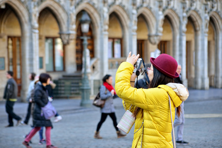 tourists stop: BRUSSELS, BELGIUM - MARCH 13, 2015: Foreign tourist takes pictures on Grand Place in Brussels. Cold weather does not stop tourists to visit Belgium