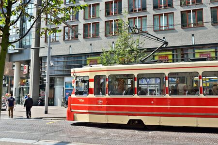 catchlight: HAGUE, NETHERLANDS-AUGUST 01, 2014: Red tram moves by street in center of Hague.