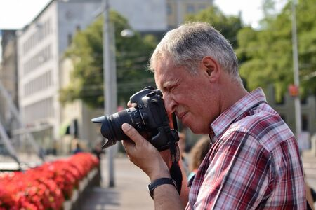 catchlight: HAGUE, NETHERLANDS-AUGUST 01, 2014: Unidentified tourist takes pictures in historical center of Hague with his Canon 7D camera. Editorial