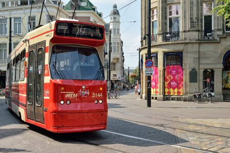 catchlight: HAGUE, NETHERLANDS-AUGUST 01, 2014: Red tram moves by street in historical center of Hague. Editorial