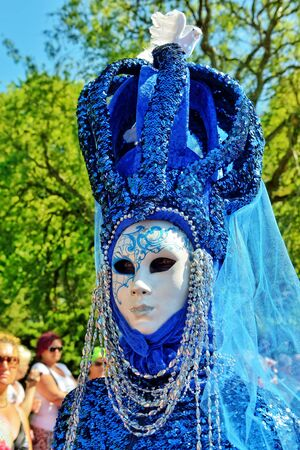 communal: MOUSCRON, BELGIUM-JUNE 06, 2015: Participant of Venice in Mouscron promenade in Parc Communal demonstrates costume of venetian carnival Editorial