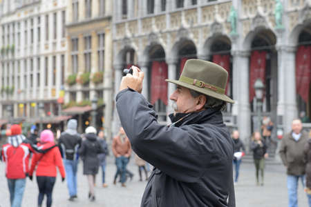 BRUSSELS, BELGIUM-DECEMBER 05, 2014: Tourist taking pictures on Grand Place in Brussels, mostly popular popular attraction in the city Editorial