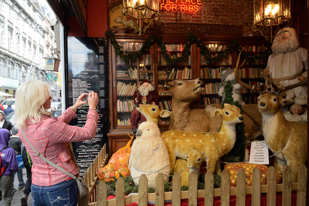 BRUSSELS, BELGIUM-DECEMBER 06, 2014: Tourist takes picture of Christmas decorations on the street in center Brussels, very popular between local people and tourists
