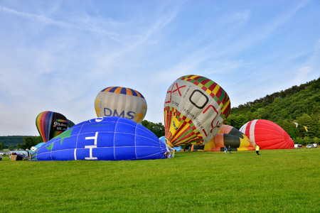 sponsors: ROCHEFORT, BELGIUM-MAY 31, 2014: Hot air balloons prepared to take off in the sky of Walloon on the field near Rochefort. Expensive sport is supported by different sponsors who place their logos on the balloons. Editorial