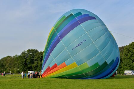 ROCHEFORT, BELGIUM-MAY 31, 2014: Hot air balloons prepared to take off in the sky of Walloon on the field near Rochefort. Expensive sport is supported by different sponsors who place their logos on the balloons. Editorial