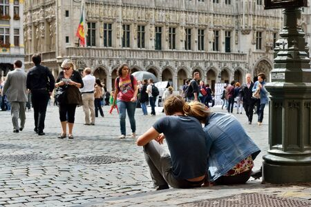 excursions: BRUSSELS, BELGIUM-AUGUST 29, 2015: Couple of tourists sitting on the pavement of Grand Place in Brussels having pause between excursions Editorial