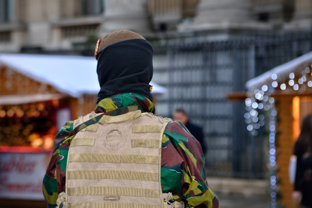 protects: BRUSSELS, BELGIUM-DECEMBER 1, 2015: Armed soldier protects Christmas Market in center of Brussels Editorial