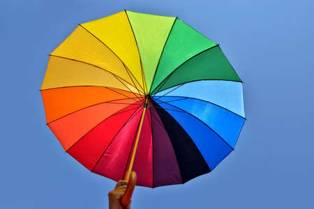 Rainbow umbrella in hand of a man on blue sky Stock Photo