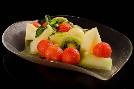 Red and yellow melon salad on a transparent glass plate