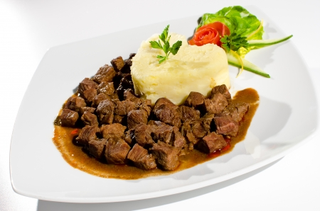Veal stew with mashed potatoes on a white plate