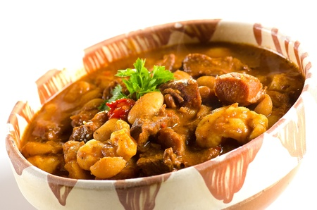 Goulash in clay pot against white background