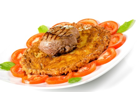 Schnitzel with medallions of beef on a bed of tomatoes photo