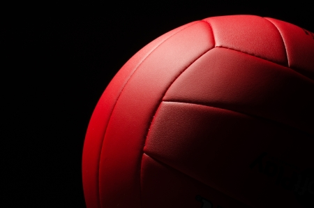 Red volley ball against a  black background photo