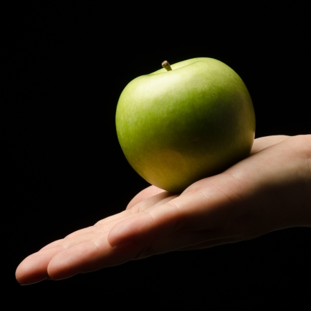 Hand holding an apple against a black background photo