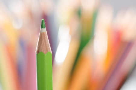 Single green pencil  against color pencils background macro photo