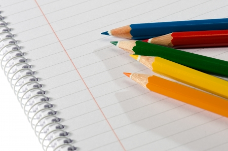 Color pencils and notebook against white background photo