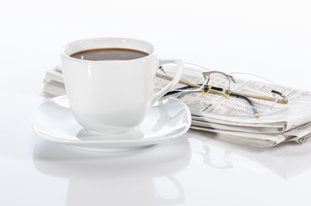 Cup  of coffee, the newspaper and the glasses isolated on white Stock Photo - 15139861