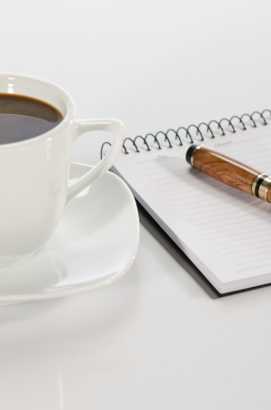 Cup of coffee, pen and notebook on white background detail photo