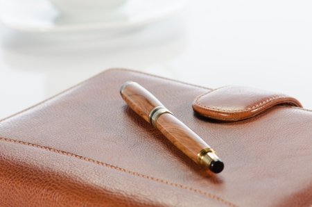 Pen and  leather notebook against a  white background photo