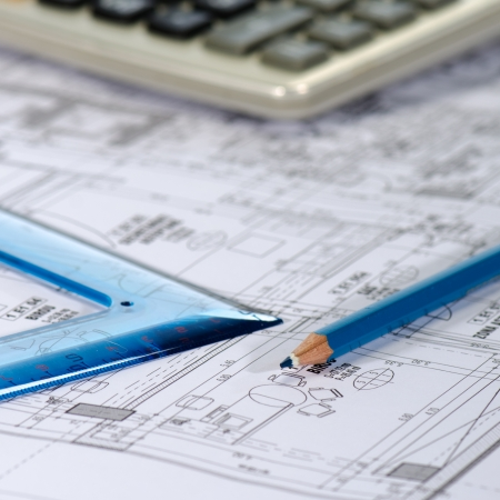 Blueprints, pencil, square drawing and calculator against a  white background