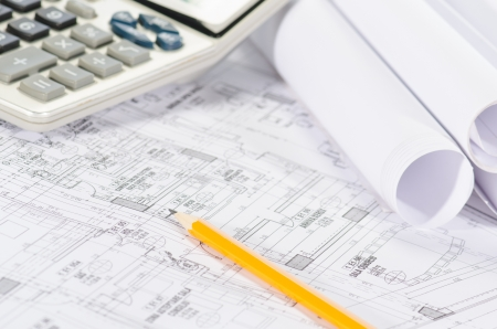 Blueprints, pencil and calculator against a  white background