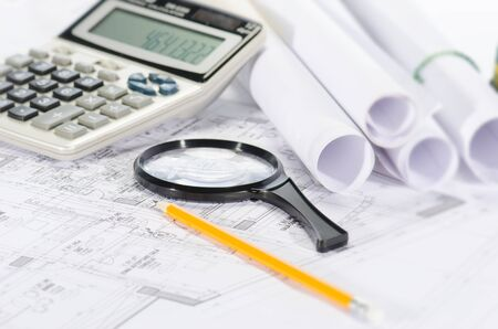 Blueprints, pencil, magnifier and calculator against a  white background photo